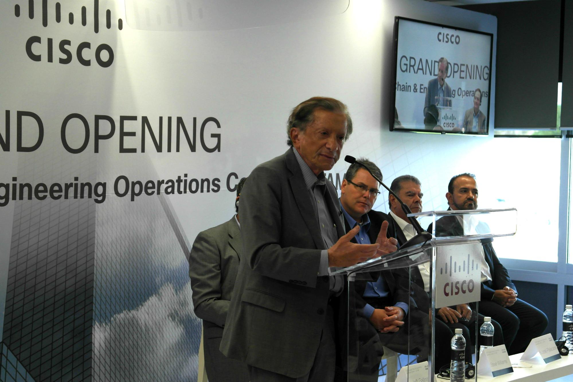 Un hombre mayor, vestido con un traje gris habla a una audiencia. Detrás de él se lee la palabra opening