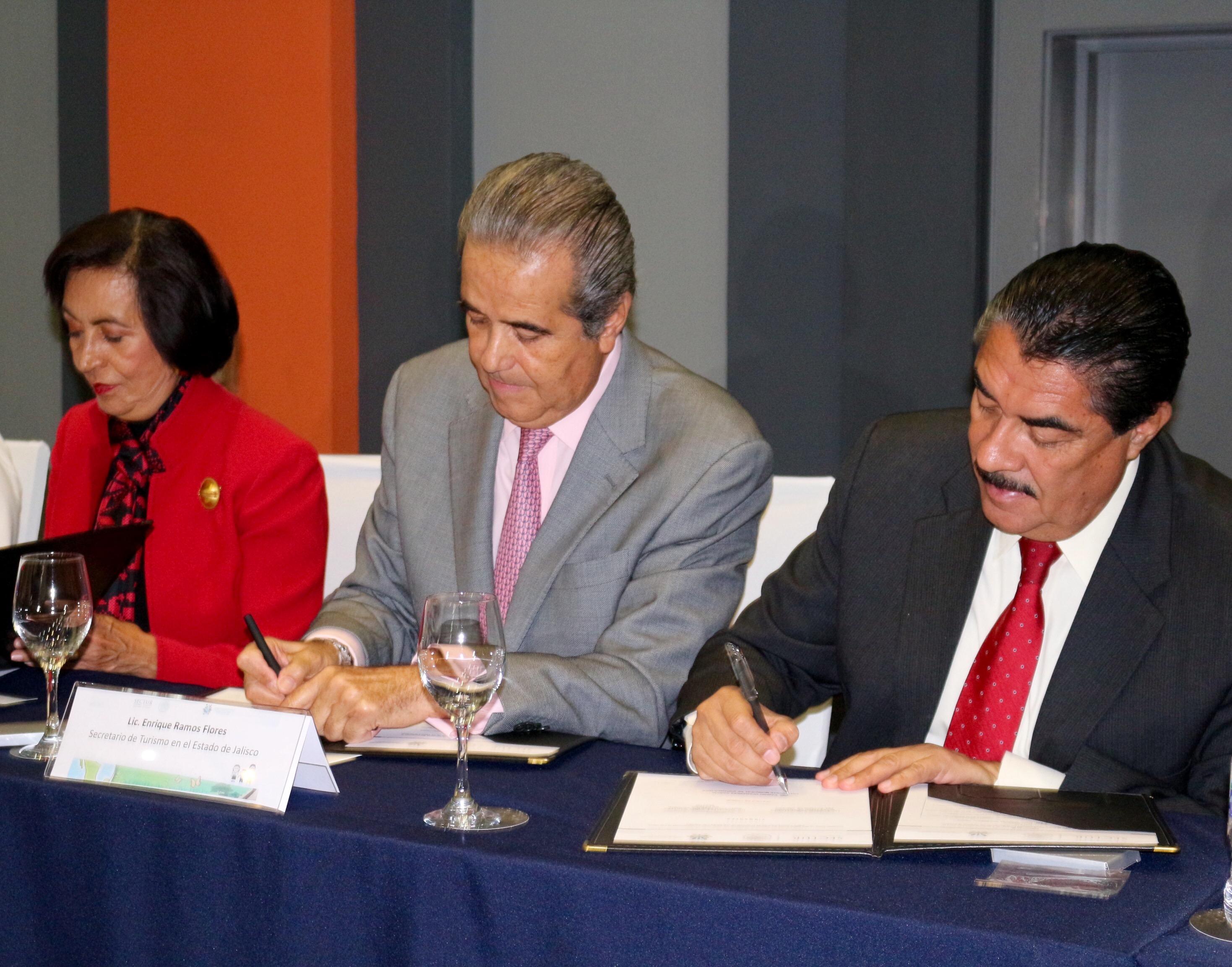 Dos hombre de traje y una mujer se encuentran firmando un papel