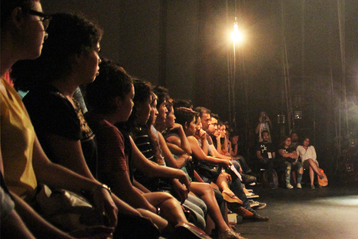 Foto de una audiencia de frente viendo una obra de teatro.