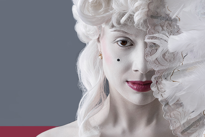 Imagen de actriz con maquillaje característico de la época del siglo 18 en la que surgió el compositor Amadeus Mozart.