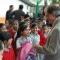Una niña recibe una mochila de manos del secretario. Hay varios niños alrededor de ella.