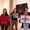 Tres mujeres sostienen cada una un cuadro bordado en tela
