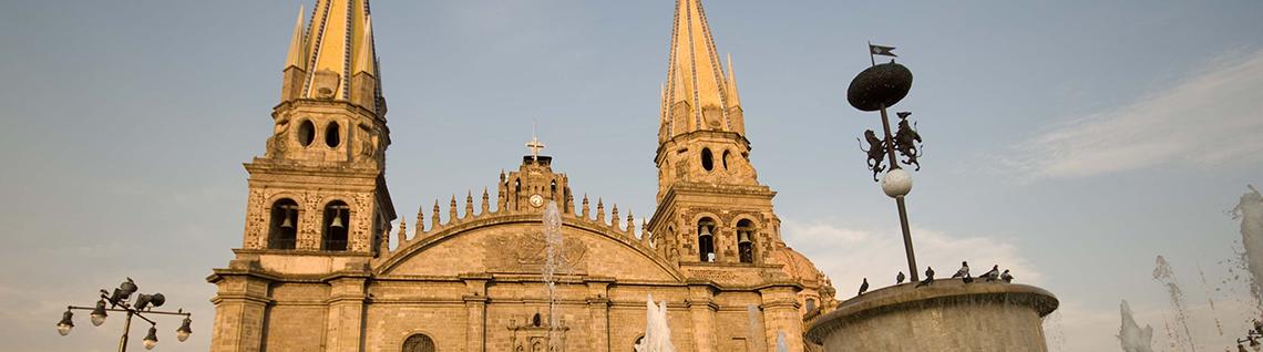 Imagen alusiva a la sección Área Metropolitana de Guadalajara, foto frontal de la Catedral de Guadalajara en el fondo,  iniciando con  la  Plaza Guadalajara en la que se muestra parte de la fuente