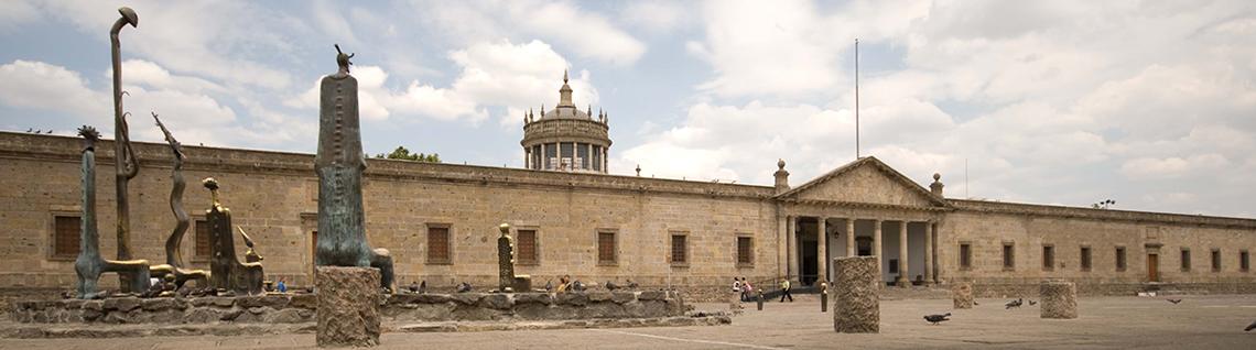 """Foto de la fachada del Instituto Cultural Cabañas, del lado izquierdo una serie de esculturas de bronce llamada """"Sala de los Magos"""" de Alejandro Colunga"""